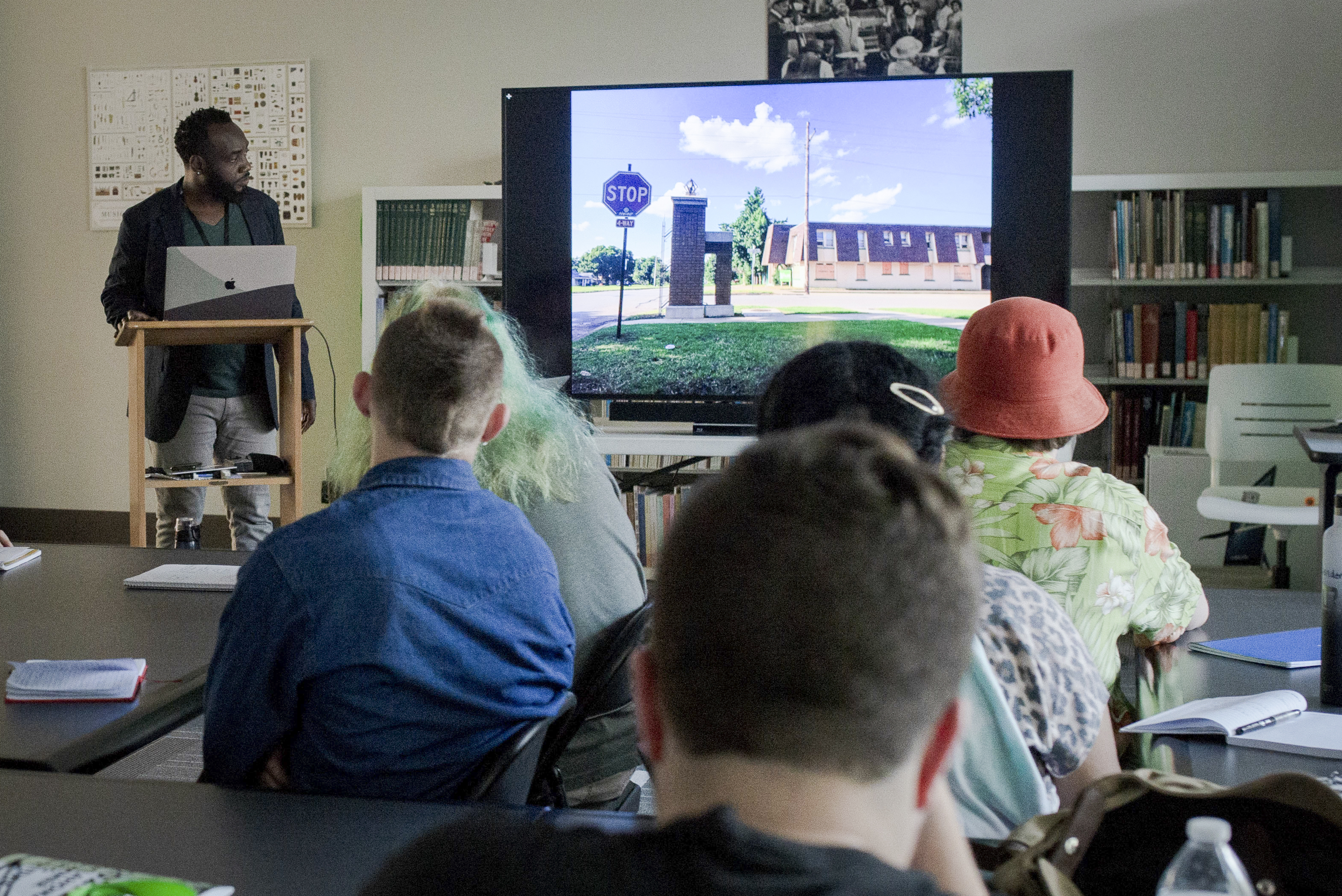 A man stands at a lectern in front of a group of students watching a film on a TV screen in a classroom setting.