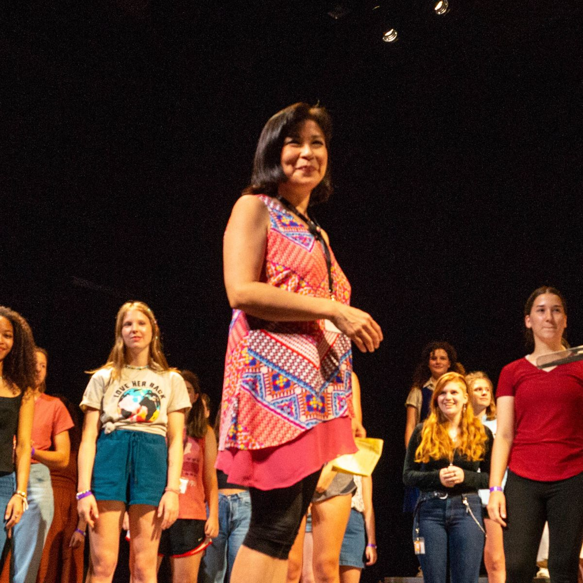 A person with dark hair and a headset mic stands in the spotlight on stage with rows of performers behind her