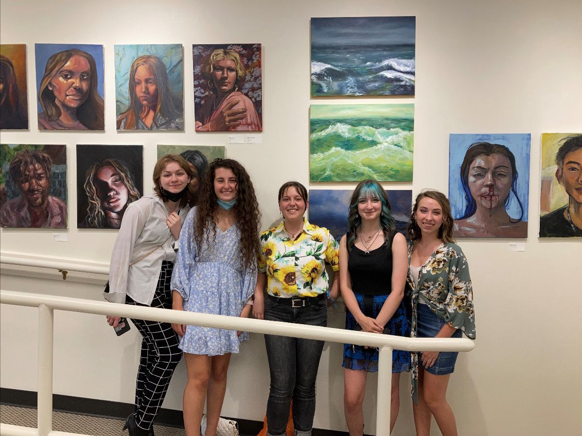 Five young people stand in front of paintings on canvas hung on a gallery wall