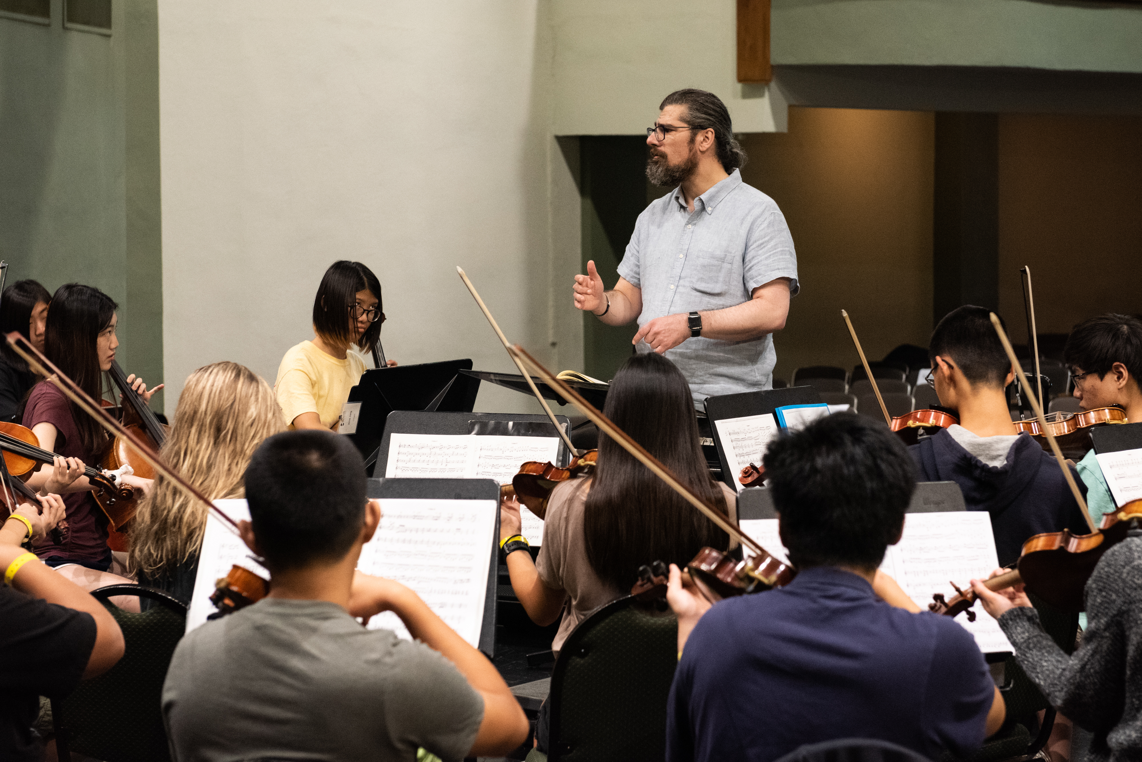 An orchestra performs indoors as the conductor directs at the front of the crowd